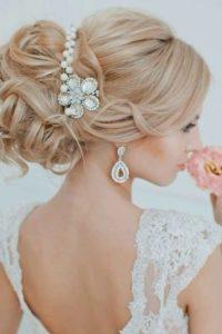 объемный пучок с дополнением заколки стилизованной под жемчуг в свадебной укладке